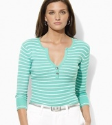 A deep split neckline finished with silver-toned buttons lends modern allure to a classic striped Henley in soft ribbed cotton.